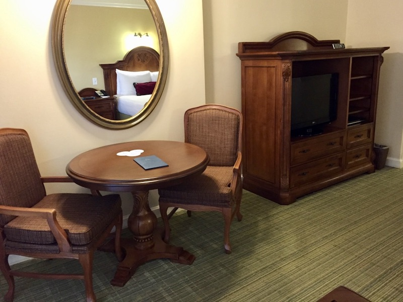 Side table with two chairs, armoire and TV